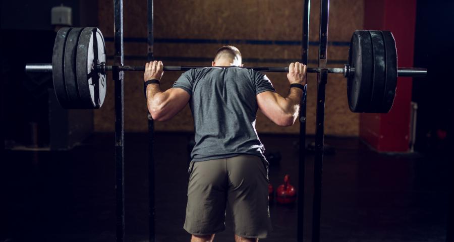 man lifting weight on cheap power rack
